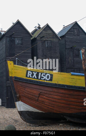 Hastings,  East Sussex, England. Winter. Fishermens huts for drying nets, with boat in front on Stade beach.