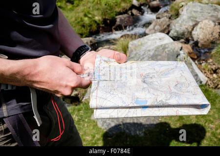 Hiker holding a hiking map and using a navigation compass to measure distance navigating on a hike in Snowdonia - Stock Photo