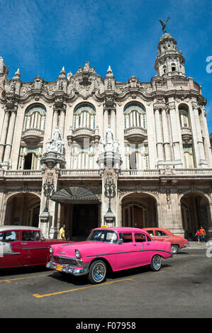 HAVANA, CUBA - JUNE 13, 2011: Bright pink vintage American car stands parked in front of the landmark Great Theater - Stock Photo