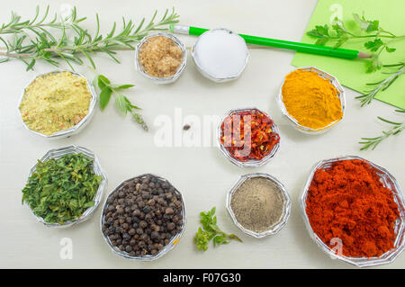 Set of different spices in shiny bowls with pen and paper for writing recipes on a white wooden table - Stock Photo