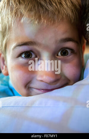 Seven year old boy peeking over the shoulder of his grandfather, with a window reflection on them, in Seattle, Washington, - Stock Photo