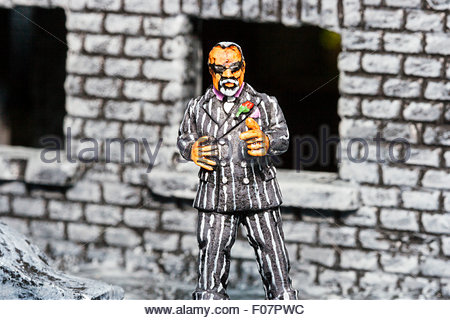 Close-up of metal painted model game figure. Sidney Greenspan (Rafm figure) model figure standing by destroyed house - Stock Photo