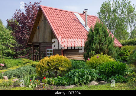 Standard no name wooden rural  shed with red tile roof  in the European decorative garden landscape. Sunny day - Stock Photo