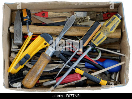 The old rusty used tools of the grandfather lie in a fragmentary cardboard box. Isolated with patch - Stock Photo