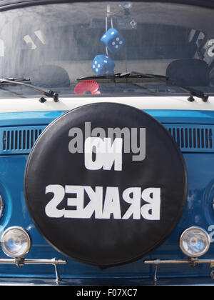 The front of a a Classic Volkswagen camper van with a sign on the spare wheel stating 'No Brakes' in reverse - Stock Photo
