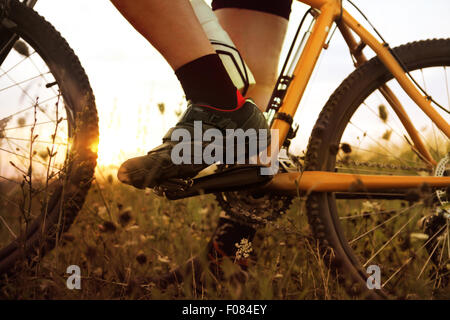 foot of traveler who stopped on field at sunset time - Stock Photo