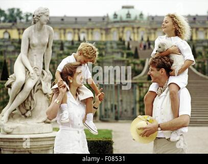 Mother and father piggy backing their children in front of sculpture, smiling - Stock Photo