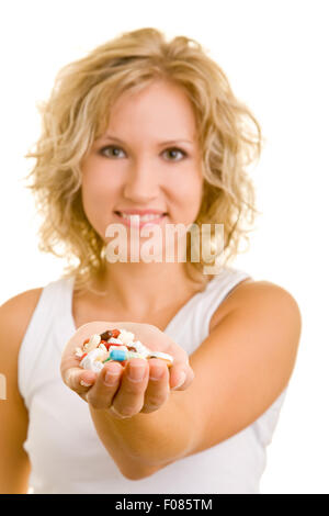 Happy woman offering different medication in palm of her hand - Stock Photo