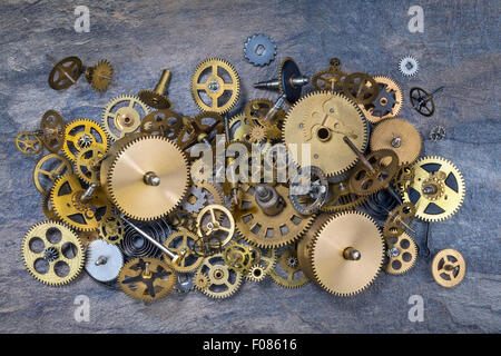 Selection of dusty old brass clock parts. - Stock Photo