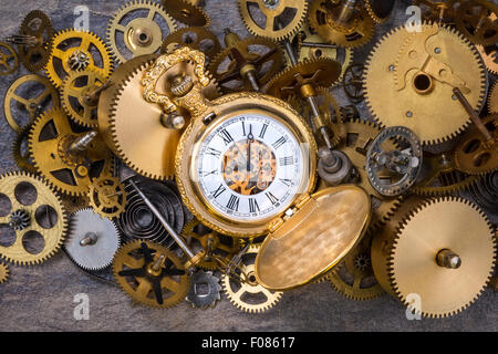 Pocket watch and a selection of dusty old brass clock parts. - Stock Photo