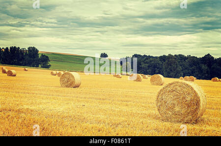 Vintage retro toned harvested field with hay bales in cloudy day. - Stock Photo