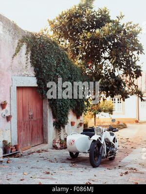 Empty motorcycle with sidecar in front of house at Portugal - Stock Photo