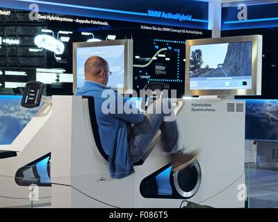 Rear view of man sitting on driving simulator in BMW World, Munich, Germany - Stock Photo