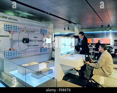 Side view of man sitting on driving simulator in BMW World, Munich, Germany - Stock Photo