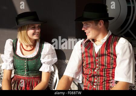 Couple wearing traditional costume looking at each other, smiling, Graz, Styria, Austria - Stock Photo