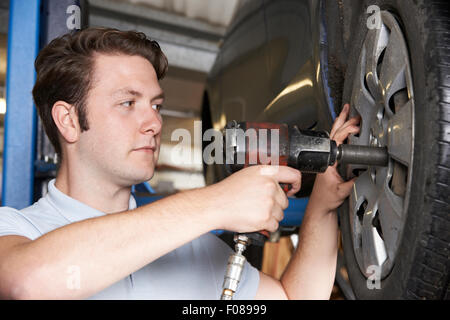 Mechanic In Garage Using Air Hammer On Car Wheel - Stock Photo
