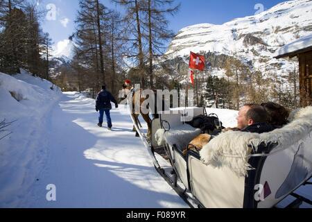 People in horse-drawn sleigh in Matterhorn in Valais, Switzerland - Stock Photo