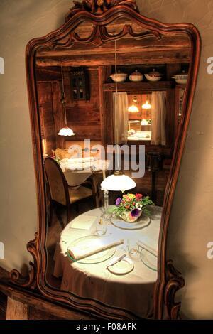 Reflection in mirror of set table at Restaurant La Stua de Michil, South Tyrol, Italy - Stock Photo