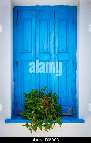 Window shutter in characteristic blue on white colors in Kokkari on the Greek Island of Samos. - Stock Photo