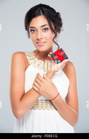 Portrait of a smiling cute woman holding jewelry gift box on gray background - Stock Photo