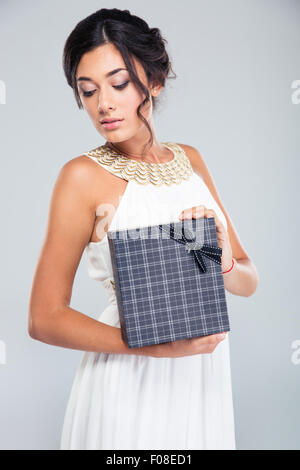 Portrait of a beautiful woman holding gift box on gray background - Stock Photo
