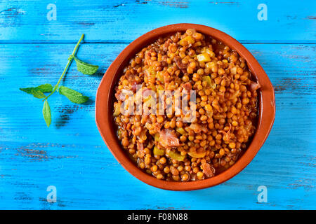 high-angle shot of an earthenware bowl with spanish lentil stew with serrano ham on a blue rustic wooden table - Stock Photo
