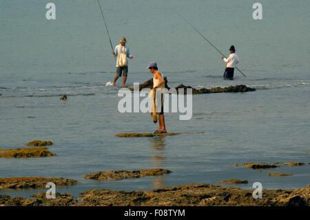 Fishermen on rocky beach. - Stock Photo