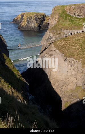 View of people at Carrick-a-Rede Rope Bridge, Antrim, Ireland, UK - Stock Photo