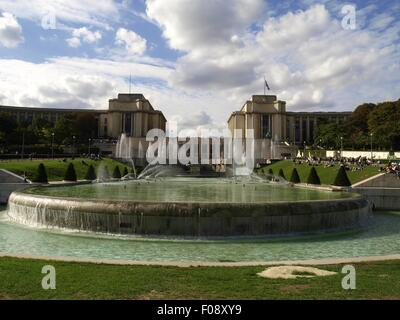 Fountain in front of the Eiffel Tower with cloudy sky in Paris, France - Stock Photo