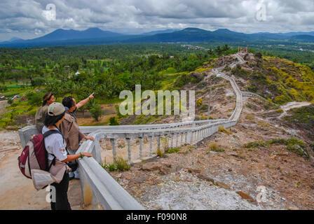 Tourists enjoying panoramic view of Minahasa from the stairways of Bukit Kasih, Kawangkoan, North Sulawesi, Indonesia. - Stock Photo