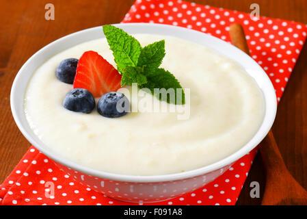 Smooth semolina porridge served with fresh fruit - Stock Photo
