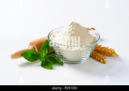 Bowl of flour, rolling pin and wheat ears - Stock Photo