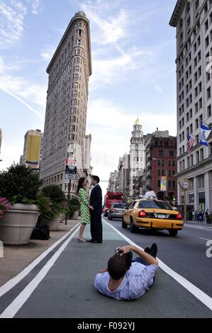 Man photographing couple standing on street in front of Flatiron Building, New York - Stock Photo