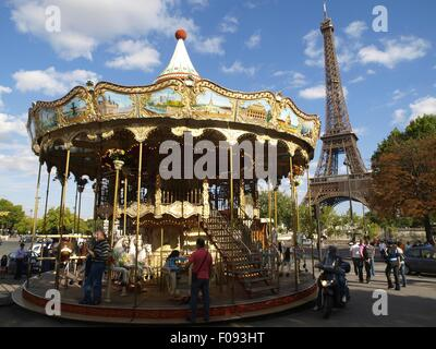 People in flying horse carousel across Eiffel Tower in Paris, France - Stock Photo