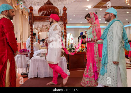 Sikh Bride and Groom Walking around the Holy Book at Wedding Ceremony in Brent Cross Gurdwara - Stock Photo