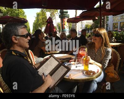 People sitting in Cafe at Avenue Champs-Elysees in Paris, France - Stock Photo