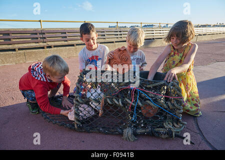 Deal, Kent, UK, Sunday 9th August 2015. Children put Cabbo masks into a lobster pot on Deal Pier, as part of the - Stock Photo