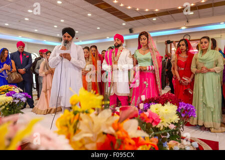 Priest with Bride and Groom at Sikh Wedding Ceremony in Brent Gurdwara London - Stock Photo