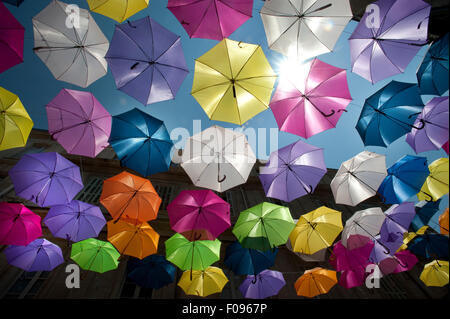 Brightly coloured floating umbrellas fill the sky above Rue Jean Jaures, Arles,Bouches-du-Rhône department, Provence, France