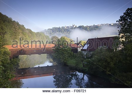 View of wooden bridge over Jagst river in Hohenlohe at Baden-Wurttemberg, Germany - Stock Photo