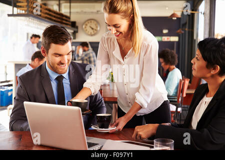 Two business people with laptop being served in a cafe - Stock Photo