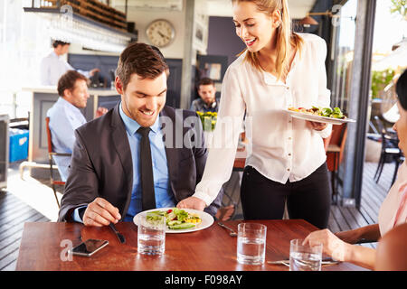 Business man being served food in a restaurant - Stock Photo