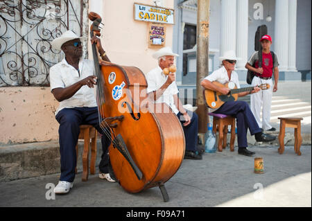 Horizontal view of a typical salsa group busking on the streets of Santiago de Cuba, Cuba. - Stock Photo