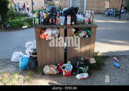 Waste bins overflowing with rubbish in a Brighton park - Stock Photo