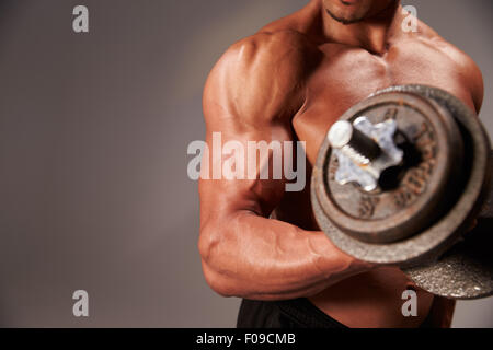 Male bodybuilder working out with a  heavy dumbbell, crop detail - Stock Photo