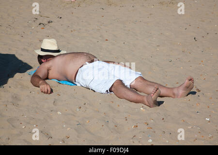 British holidaymaker enjoying the warm weather on the beach at Camber Sands, East Sussex, South England, UK - Stock Photo
