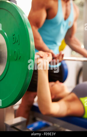 Woman lifting weights with trainer, focus on barbells - Stock Photo