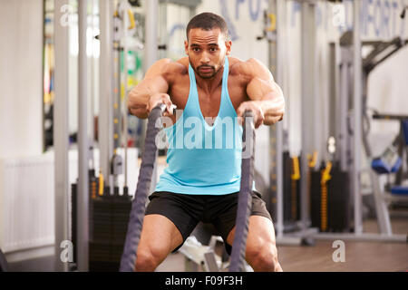 Young man prepares for work out with battle ropes at a gym - Stock Photo