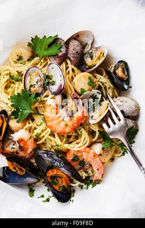 Seafood pasta - Spaghetti with clams, prawns, sea scallops on white baking parchment - Stock Photo