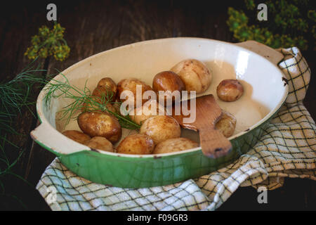 Fried young potatoes with wooden spatula and fresh dill in metal pan. Over black wooden table with checkered kitchen - Stock Photo